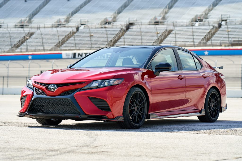 a red Toyota Camry TRD with black exterior detail parked near a race track