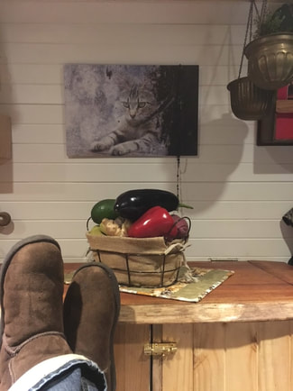 a lovely still life arrangement of peppers with the view of brown boots resting in a relaxed pose inside of the camper