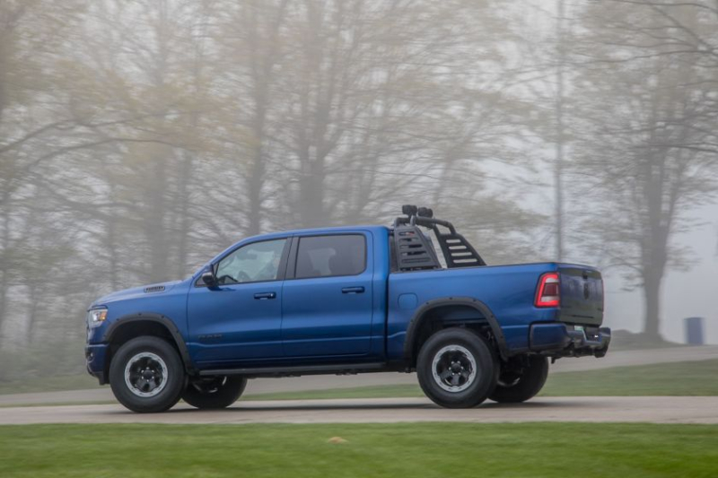 a blue Mopar ram off-road build with aftermarket accessories driving on a scenic road