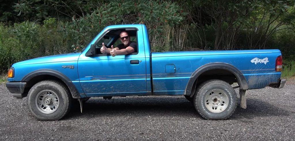 A man gives the thumbs up through the side window of a blue Ford Ranger pickup.
