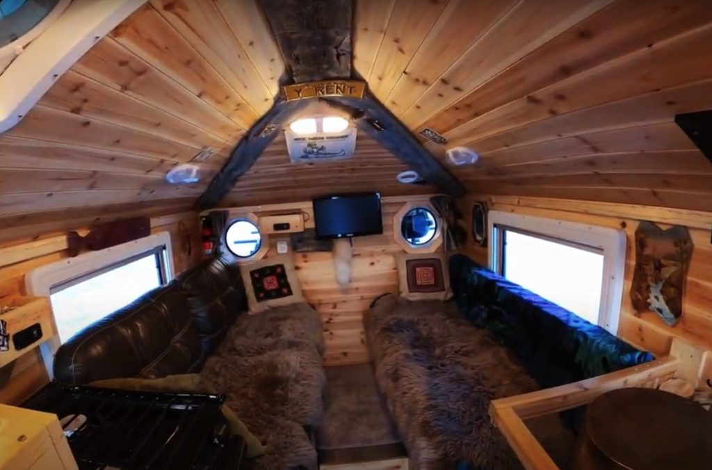 the wooden interior of the roomy hangout space inside of the Alaskan overland RV cabin