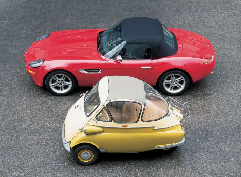 A red BMW Z8 convertible parked next to a yellow-and-tan BMW Isetta