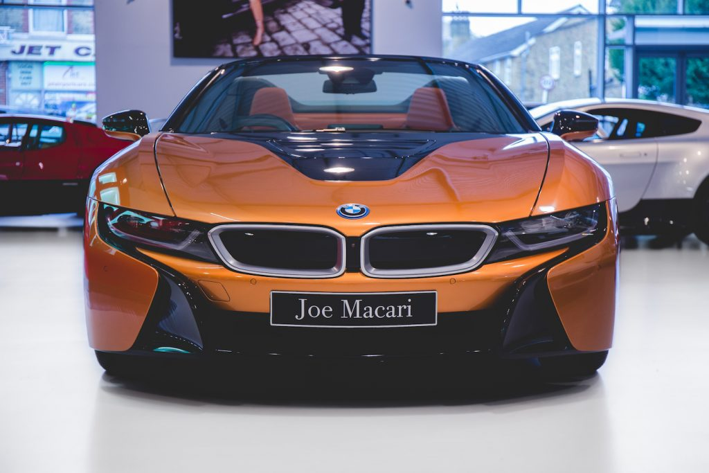 The BMW i8 in the Joe Macari Performance Cars Showroom. The BMW i8 was designed by Benoit Jacob and the production model was unveiled at the 2013 International Motor Show in Germany. It features butterfly doors, head-up display, rear-view cameras and partially false engine noise