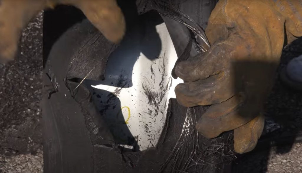 A worn tire has a large hole in it from a blowout.