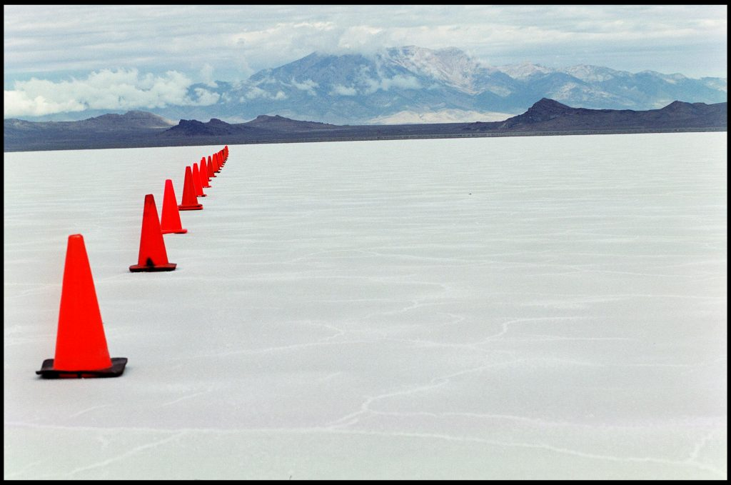 A flat white long field dissappears to the base of mountains in the background. One side is lined with traffic cones set for competition.