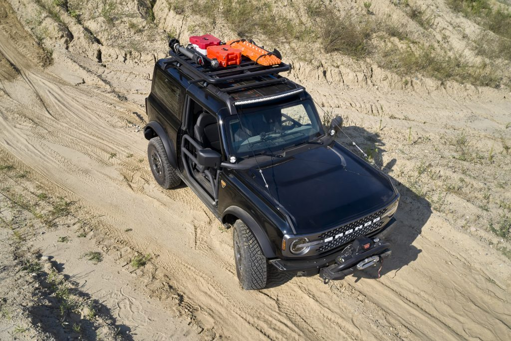 A black, two-door 2021 Ford Bronco with tube doors on a dirt road can be seen from above.