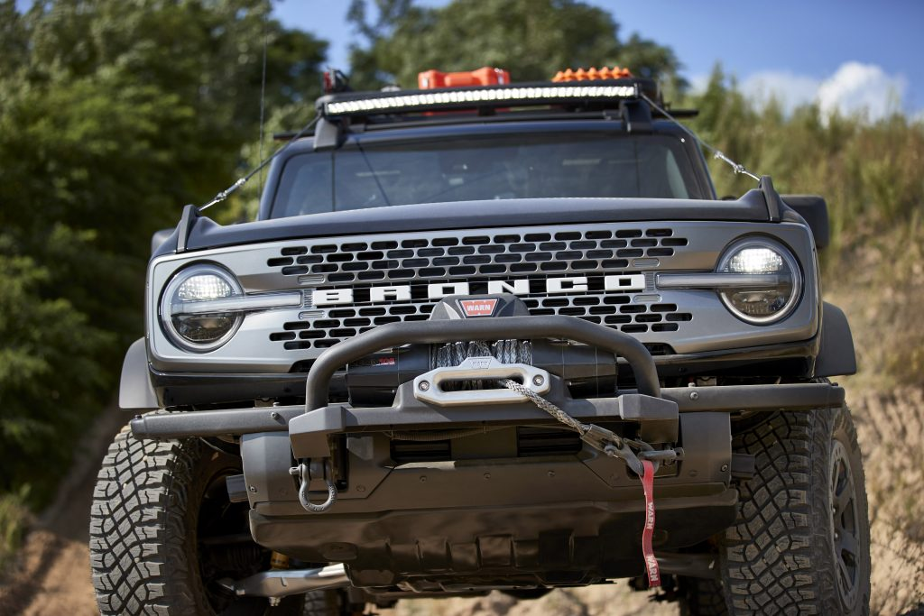 A head-n view of a black 2021 Ford Bronco with a aftermarket bumper and winch.
