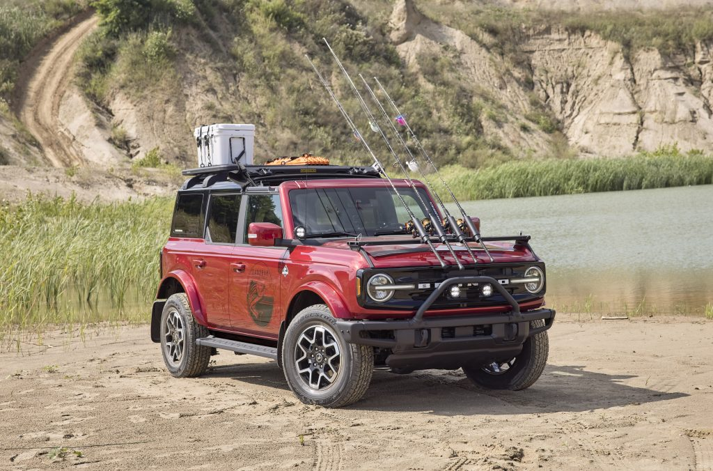 A red, four-door, 2021 Ford Bronco has the front top folded back and a custom fishing rod holder mounted on its hood. Ford is showing the Bronco is just as capable off-road as by a lakeside.