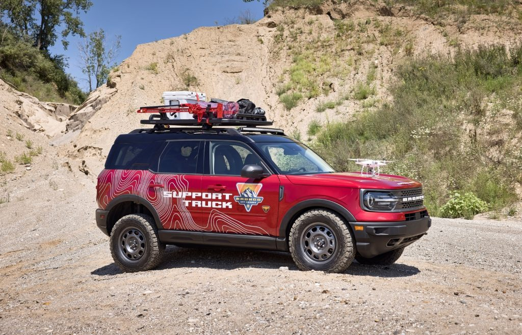 A red SUV with a roof rack and a lift kit traverses loose gravel.