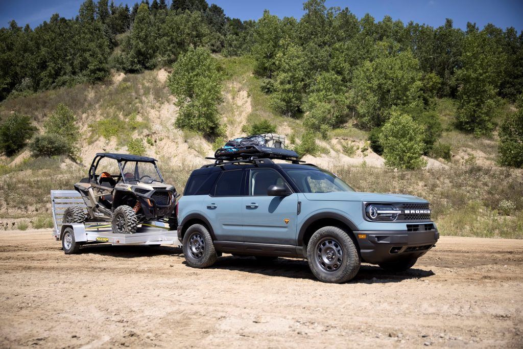 A gray 2021 Ford Bronco Sport has a roof rack and is towing a side-by-side.