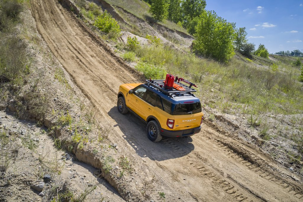 A yellow 2021 Ford Bronco Sport with a roof rack and bump guard travel a dirt road.