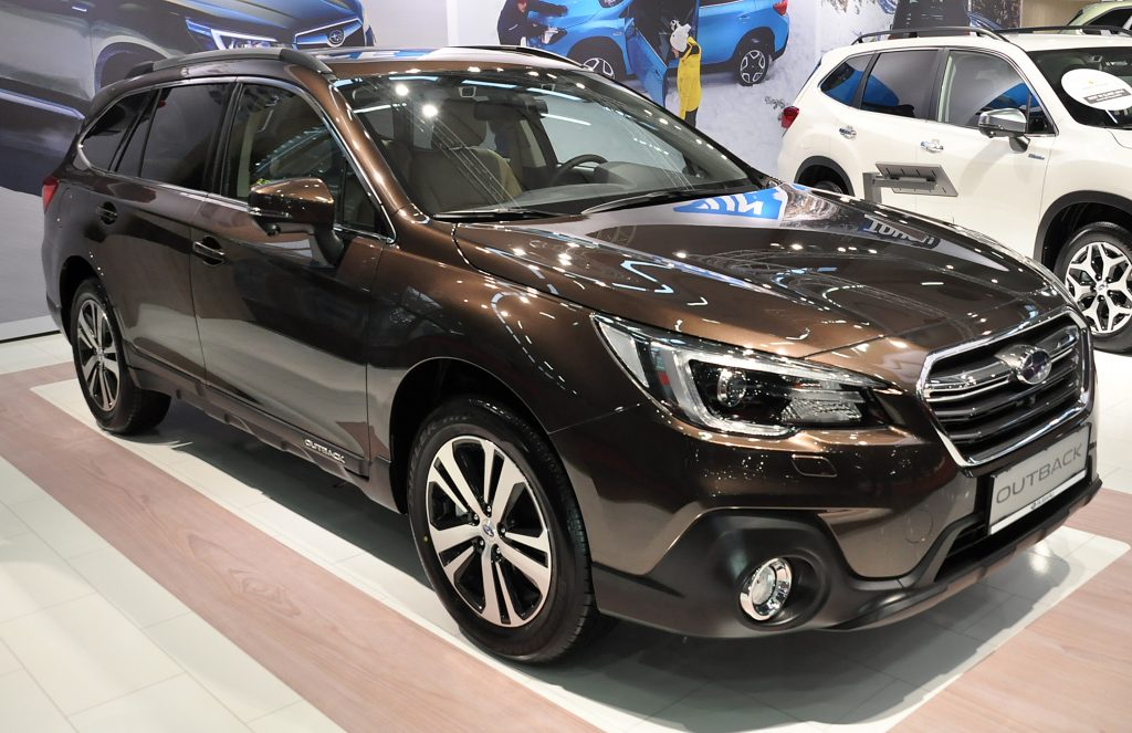 A brown Subaru Outback on display at an auto show