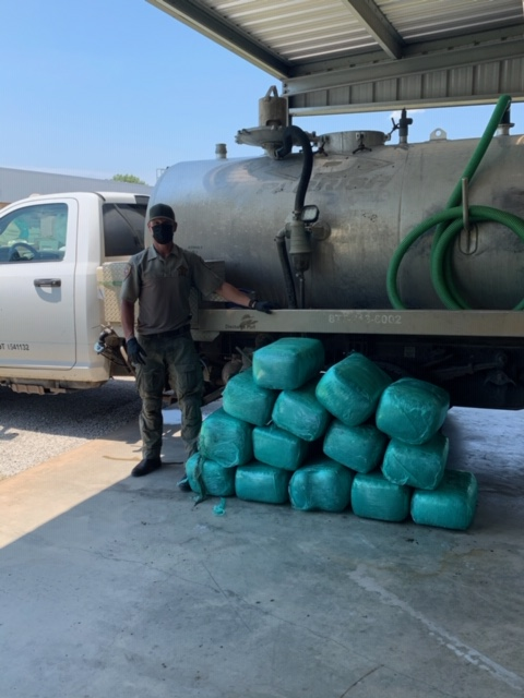 An police officer stands by bundles of drugs that were found in a septic truck tank.