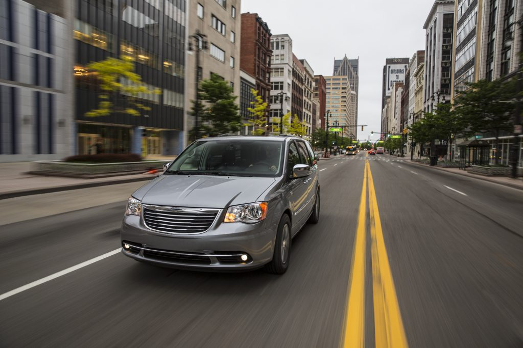 a 2015 silver town and country driving in the city. This is one of the best used minivans to buy.