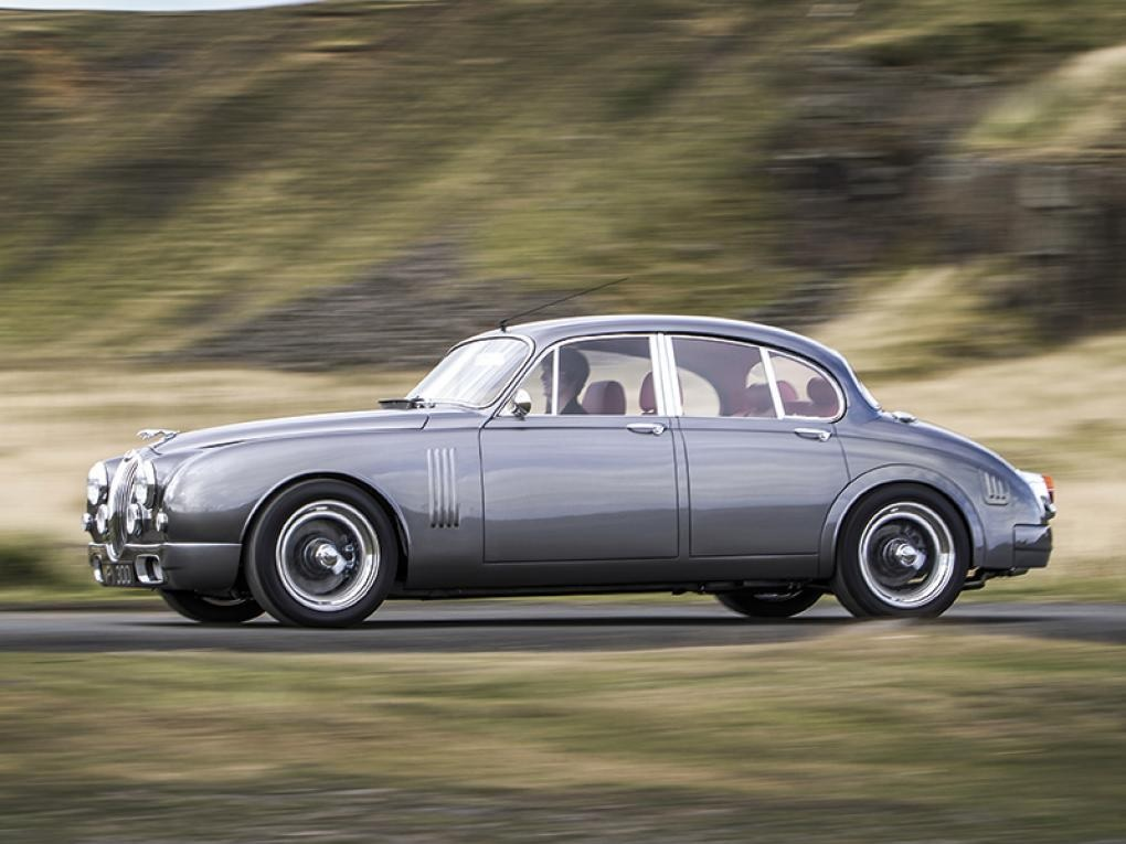 A silver CMC Jaguar Mk2 by Callum drives through the British countryside