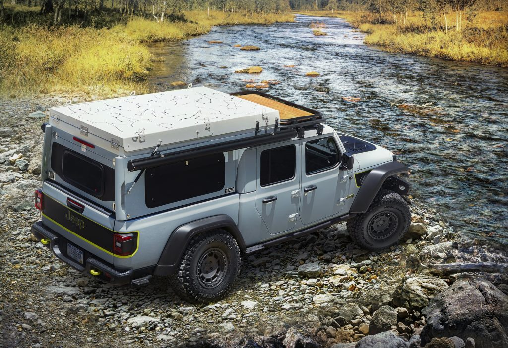 A gray Jeep Gladiator pickup is parked on bank of a creek.
