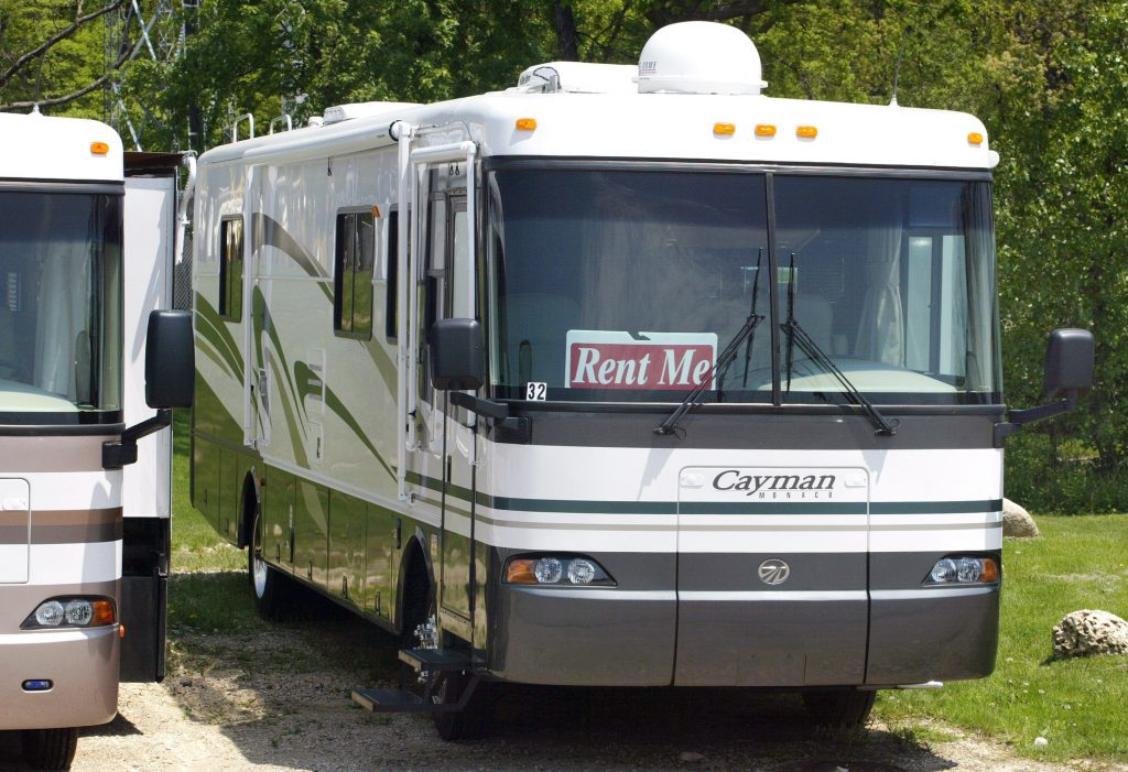 A camper with a rental sign in the windshield
