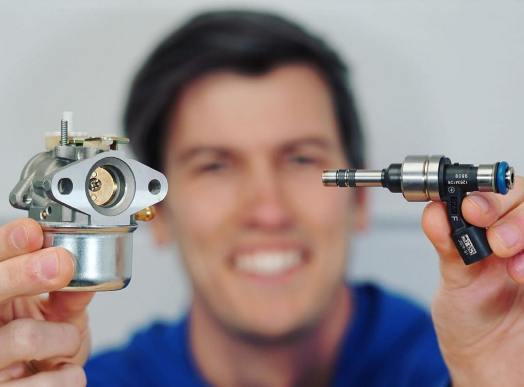 Jason Fenske of Engineering Explained holds a carburetor in his right hand and an electronic fuel injector in his left hand