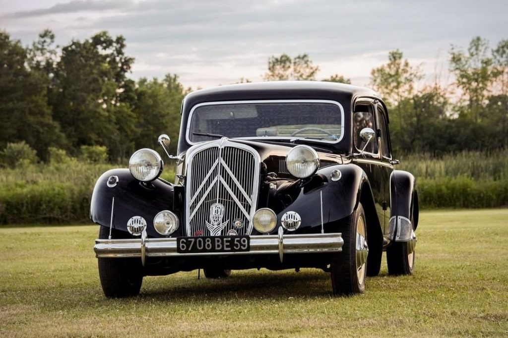 A black Citroen Traction Avant 15/6 parked in a grassy field