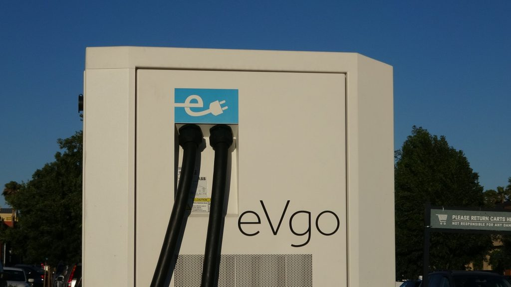An EVgo station is pictured against a sunny background.