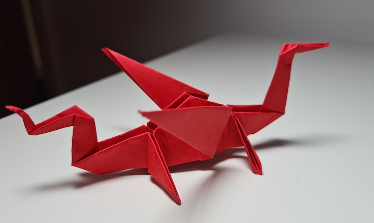 Stunning photo of an intricate red origami dragon on a white surface.