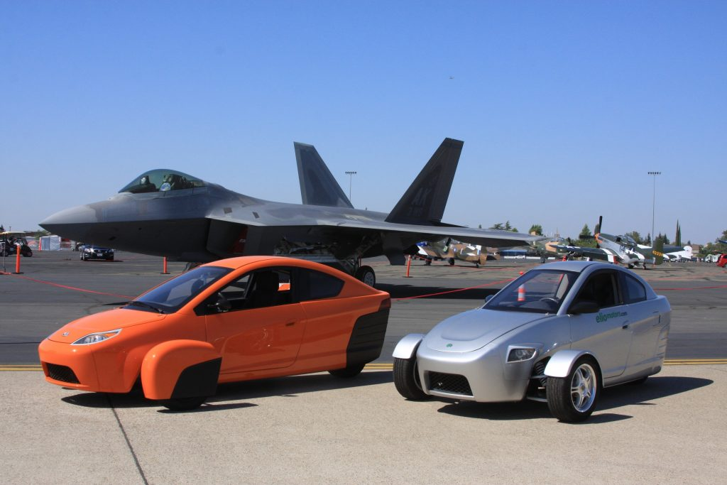 Two Elio Protypes sit on a tarmac before a parked fighter plane.