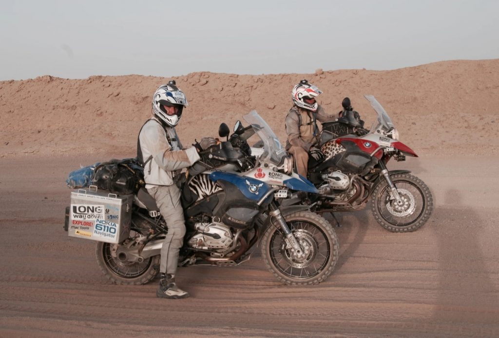 Ewan McGregor and Charley Boorman with their blue and red BMW R1200GS Adventures in the desert