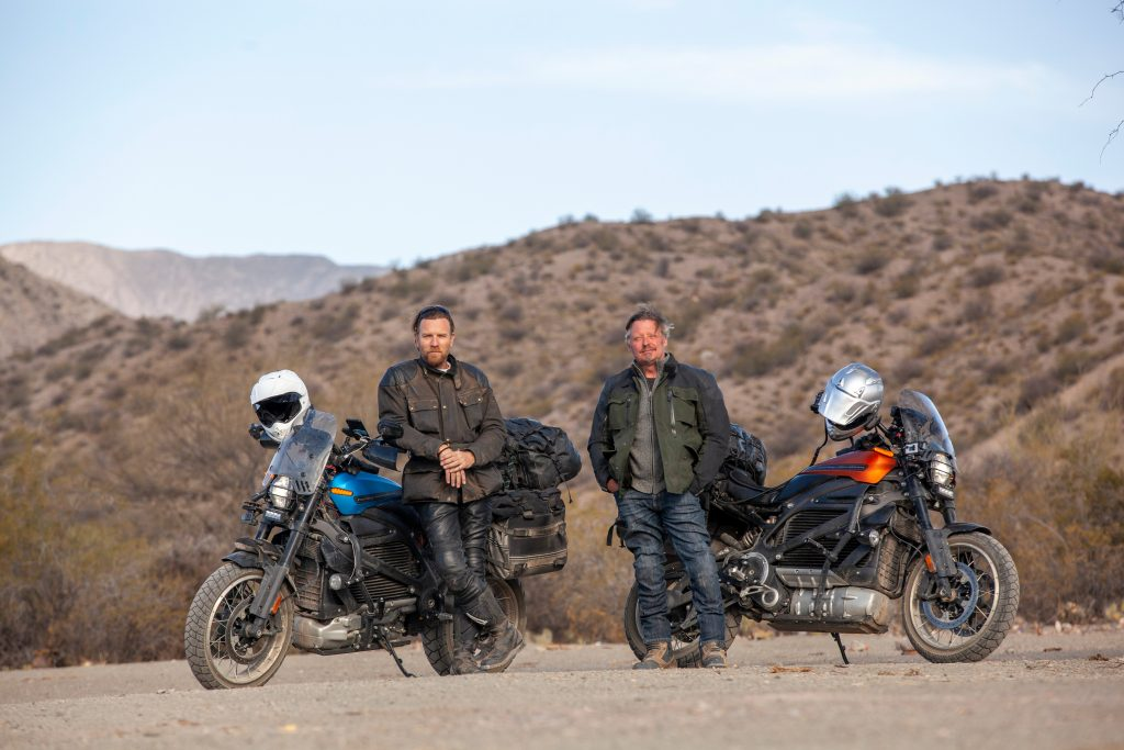 Ewan McGregor and Charley Boorman standing in front of their blue and orange Harley-Davidson LiveWires in the middle of the desert