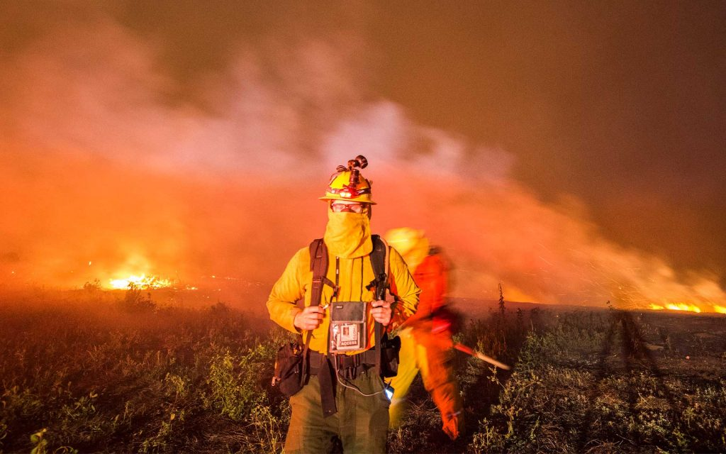 A firefighter in wildfire gear and camera in tow with a raging forest fire in the background