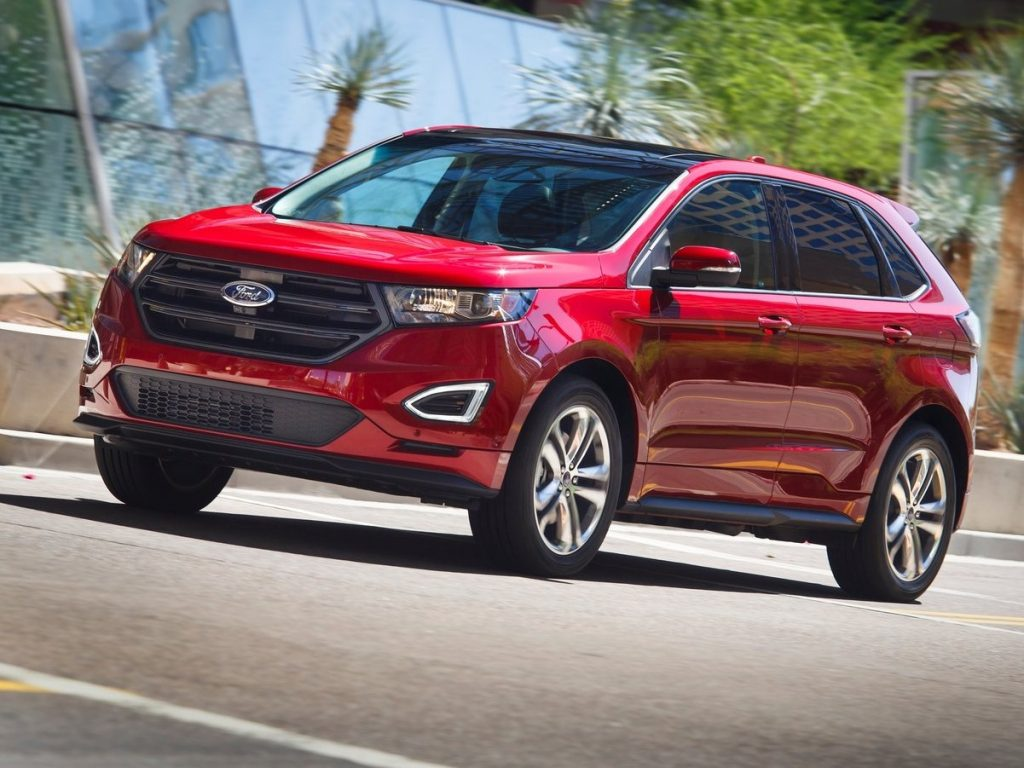 A red 2015 Ford Edge parked by a glass building.