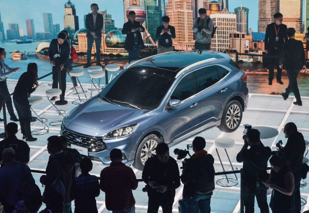 This photo taken on April 3, 2019 shows photographers taking photos of a new Ford Escape car during a press conference in Shanghai