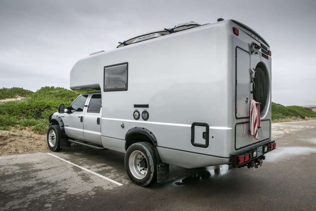 A custom Ford F-550 camper parked at a camp site