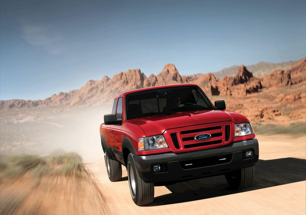 a red Ford Ranger pickup travels down a dirt road.