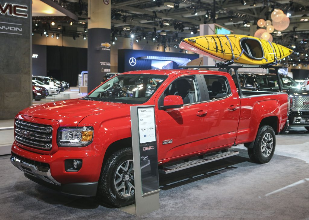 A red GMC Canyon on display at an auto show