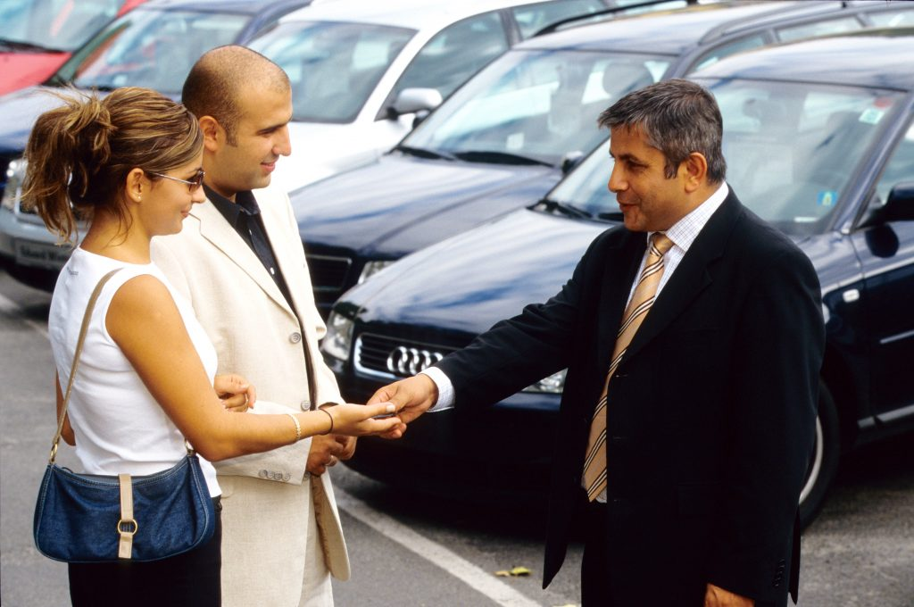 a car dealer shakes hands with clients.