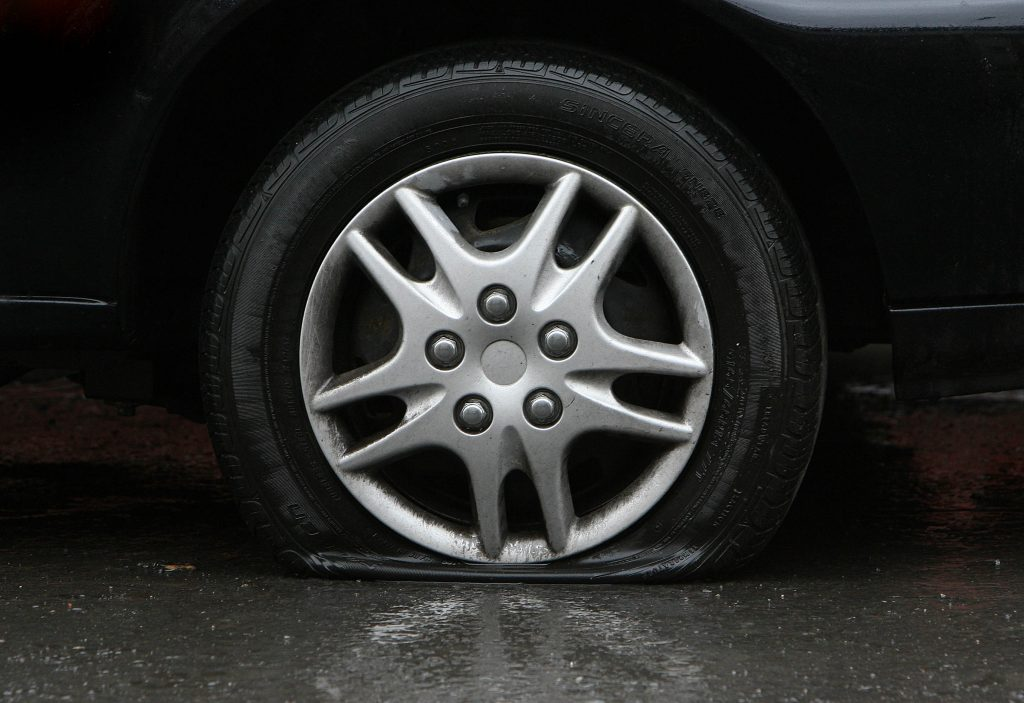 A flat tire on a car is seen on a wet pavement surface.