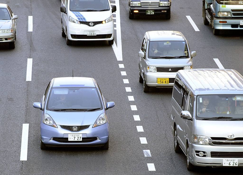 A Honda 'Fit' (L) is driven down a road in Tokyo on February 4, 2011. In January the Honda 'Fit' replaced Toyota's popular hybrid 'Prius' model as Japan's top selling car, a title that the Toyota model had held since May 2009, the Japan Automobile Dealers' Association said in a monthly report. AFP PHOTO / TOSHIFUMI KITAMURA (Photo credit should read TOSHIFUMI KITAMURA/AFP via Getty Images)