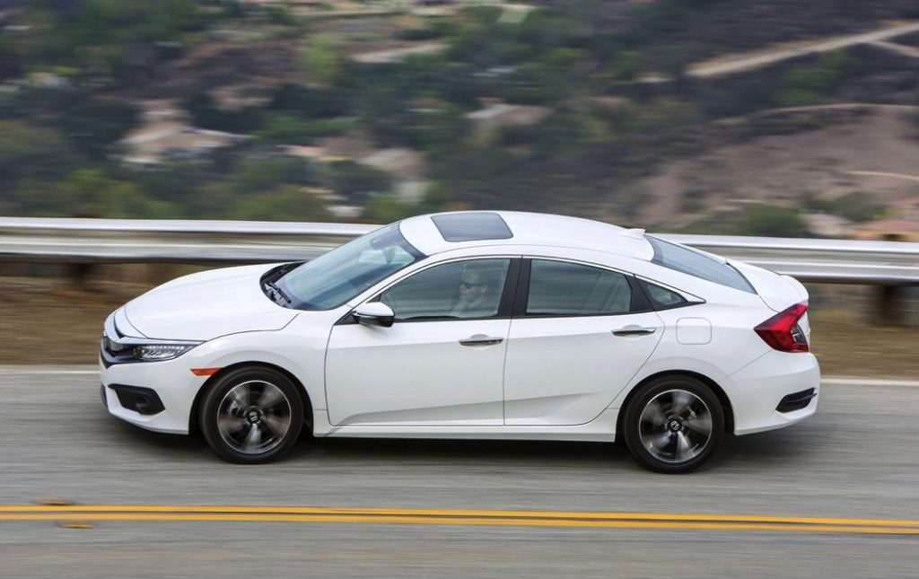 2016 Honda Civic side view from above as it drives on a scenic mountain road