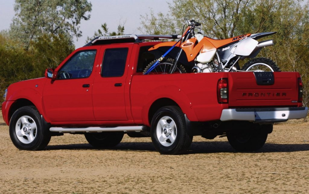 a red crew cab Nissan Frontier from the 2004 model year with a dirt bike in the back is a perfect example of one of the best used pickup trucks to buy