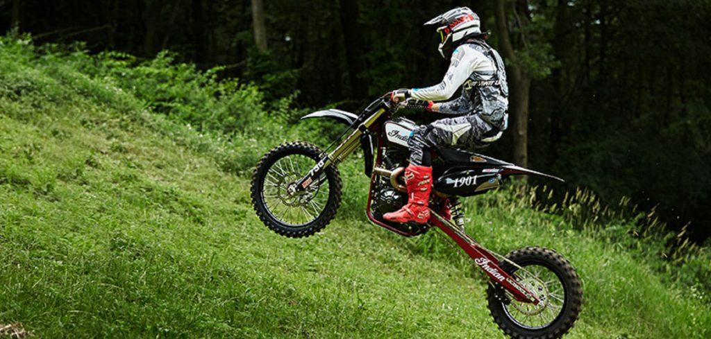 A black Indian FTR750 hill climb bike speeds up a grassy hill