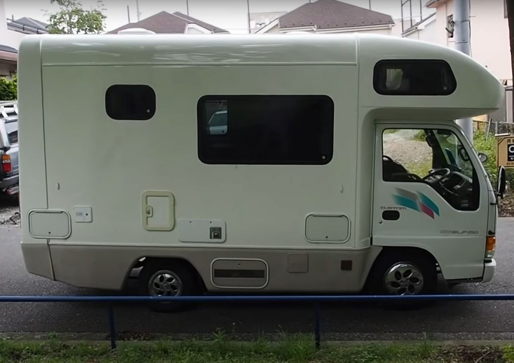 A small, white Isuzu RV is viewed from the front passenger's side.
