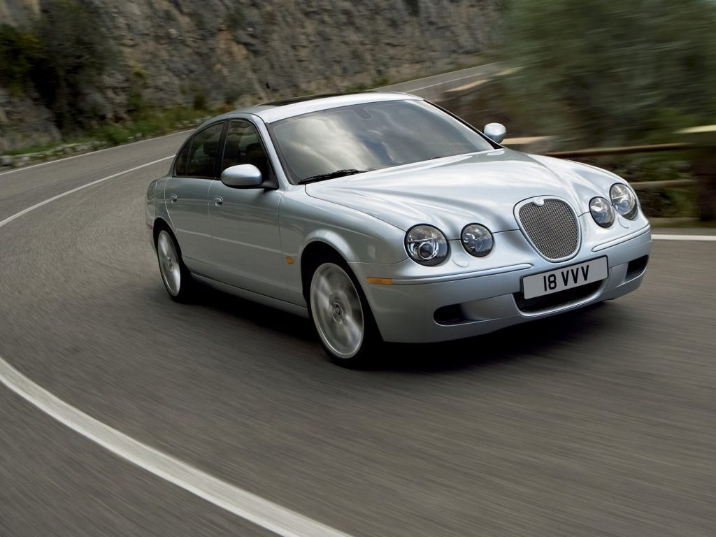 A silver Jaguar S-Type is pictured coming around a bend in the road.