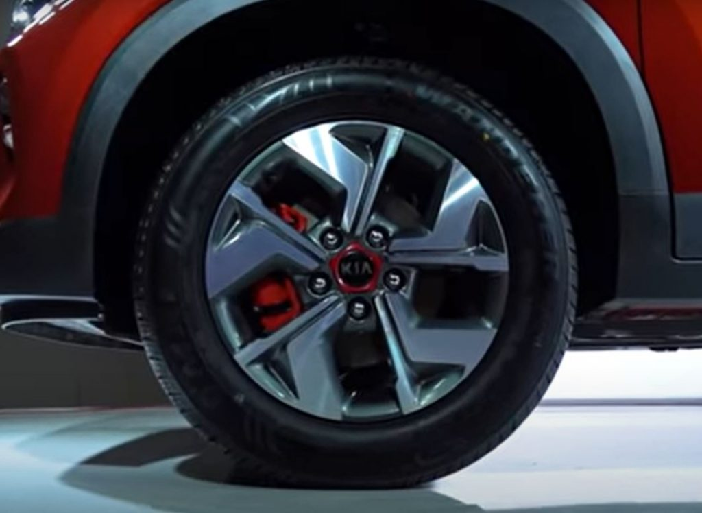 A red brake caliper is tucked in behind a silver wheel with a red accented center cap that says, Kia.