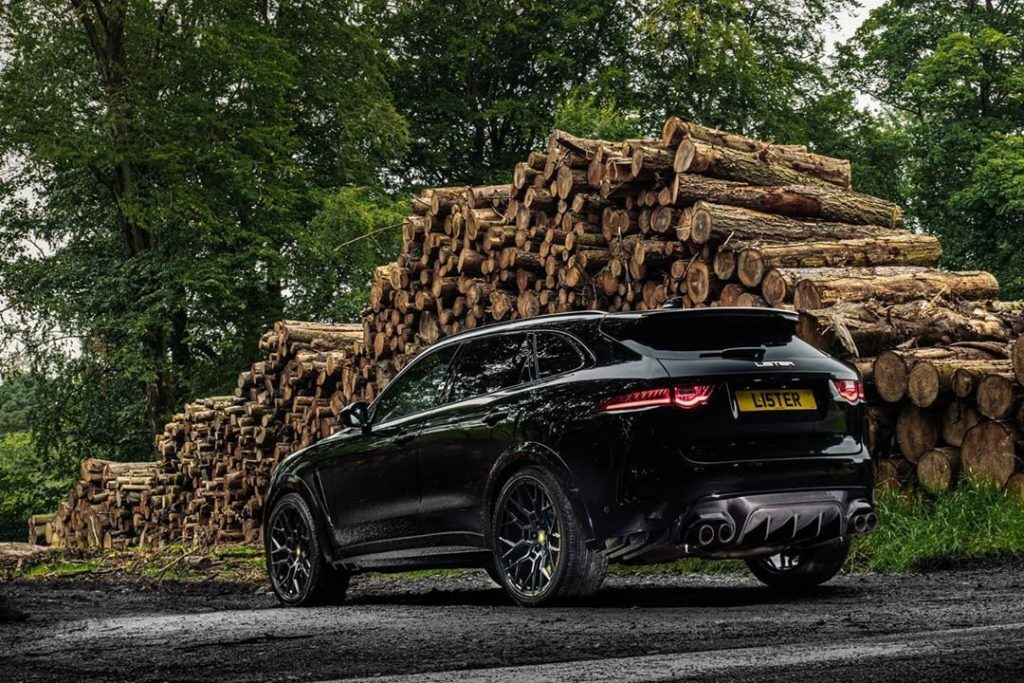 The rear view of a black Lister Stealth in front of a pile of cut logs