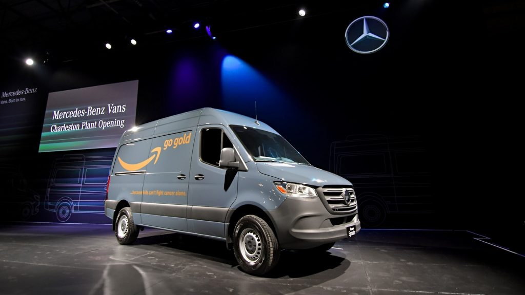 A gray Mercedes-Benz van sits on stage under spotlights.