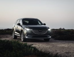 a gray 2020 Mazda CX-9 SUV driving on a gravel road in the countryside