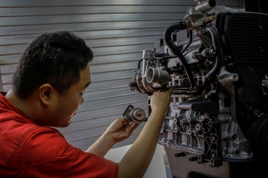 Mechanic tunes up an old Galloper engine for one of the Korean cars