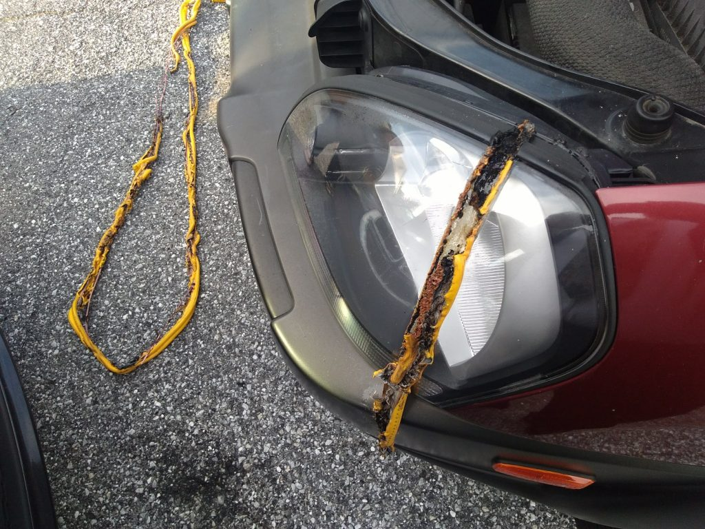 A headlight and bumper show damage after jumper cables were hooked up to a battery backwards to charge a car.