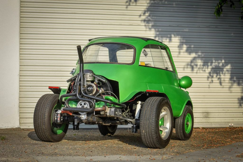 The rear view of a green modified 1957 BMW Isetta, showing the Volkswagen Beetle engine and subframe