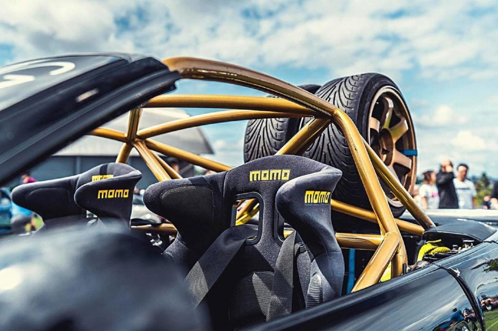 Black Momo racing seats with harnesses in a BMW E30 M3 with a gold roll cage